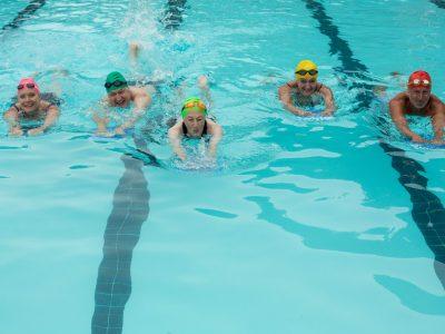 People with kickboards swimming in pool